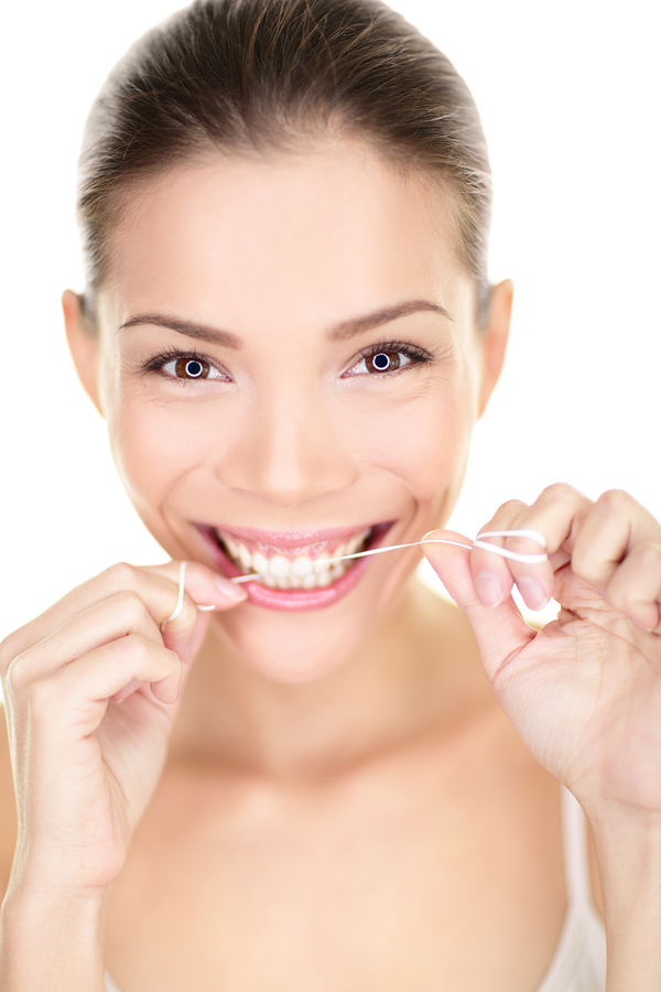 Woman flossing teeth smiling using dental flush. Happy girl with perfect teeth and toothy smile. Dental care portrait of beautiful multiracial Asian Caucasian female isolated on white background, 20s.